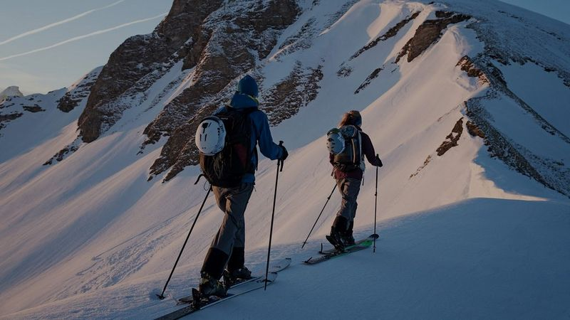 Two cross-country skiers travel along the narrow spine of a mountain, using their poles.